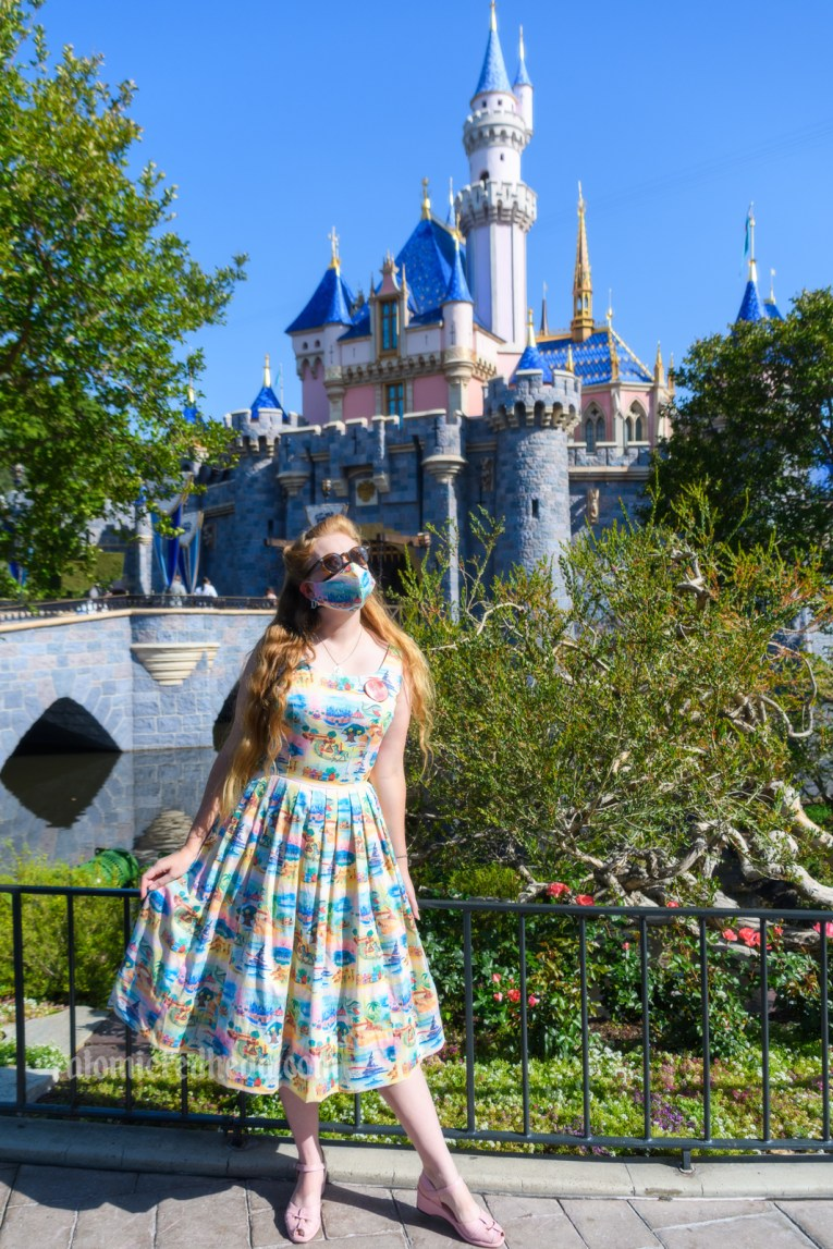 Myself standing in front of Sleeping Beauty Castle, wearing a sun dress featuring various icons of Disneyland printed on it, including Sleeping Beauty Castle, the Matterhorn, a rocket, and more.