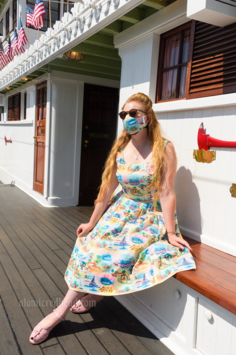 Myself seated on the riverboat the Mark Twain, wearing a sun dress featuring various icons of Disneyland printed on it, including Sleeping Beauty Castle, the Matterhorn, a rocket, and more.