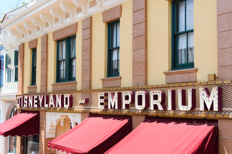 Bulbed letters spelled out 'Disneyland Emporium' along the side of a yellow building.
