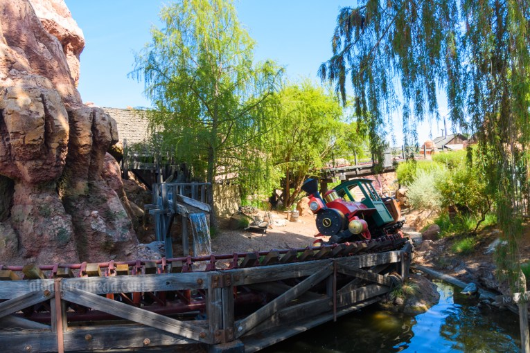 A train comes speeding around a banked track and into a cave at Big Thunder Mountain Railroad.