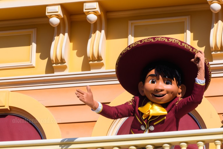 Miguel of Coco waves from the balcony of the Golden Horseshoe, wearing a maroon mariachi outfit with gold tie and gold trim.