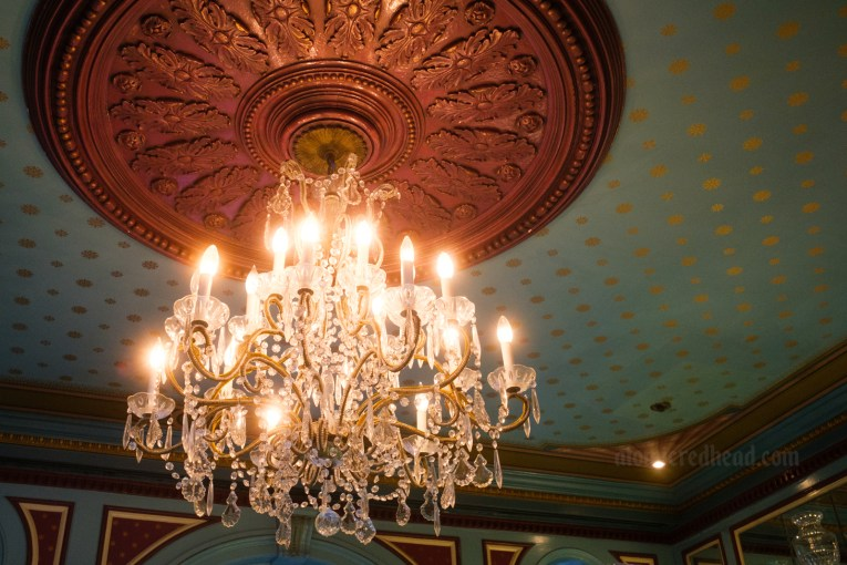 A crystal chandelier hangs from a teal and gold ceiling in New Orleans Square.