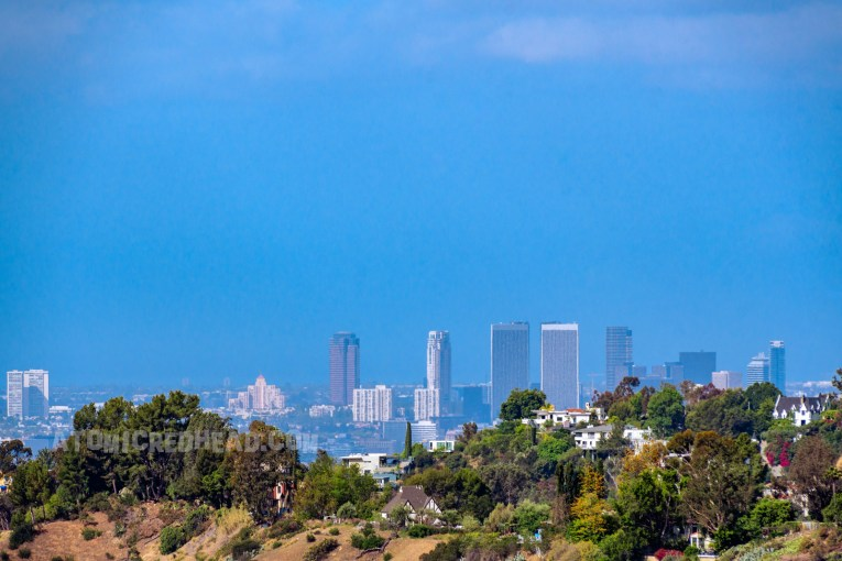 The skyscrapers of downtown Los Angeles peek from behind green hills.