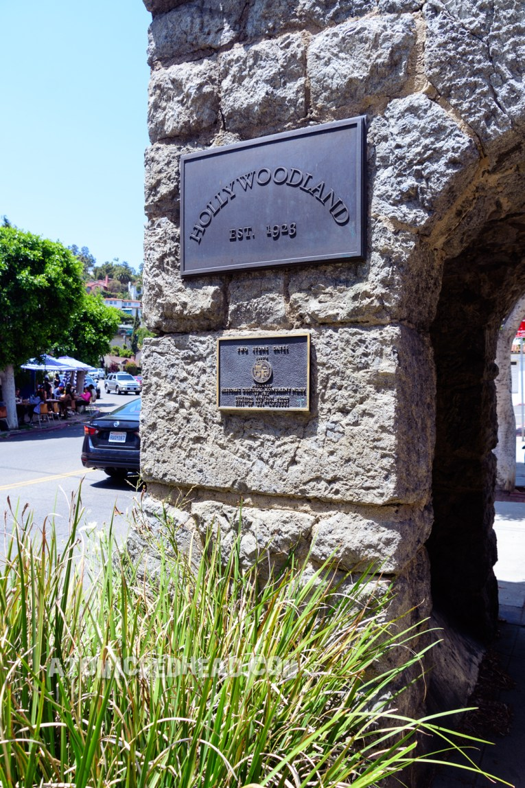 """The stone archway on the sidewalk that marks the entrance to Hollywoodland. A sign reads """"Hollywood Est. 1923"""" and another sign below reads """"Two Stone Gates 1920s Declared Historic Cultural Monument No. 20 by the Cultural Heritage Board Municipal Art Department City of Los Angeles."""""""