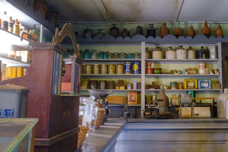 Inside the general store, with shelves stocked with various goods, and a cash register on the left.