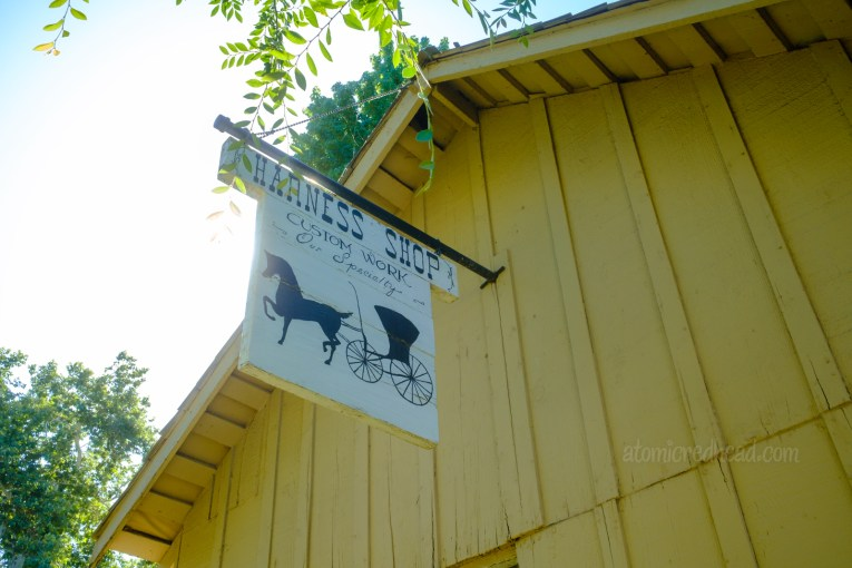 """A white sign hangs from a yellow peaked roof, featuring a horse and buggy with script reading """"Harness Shop Custom Work Our Specialty"""""""