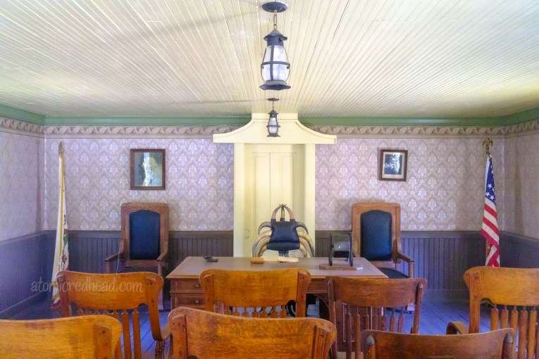 Interior of the old Kern County Court House. Purple wallpaper surrounds a chair made of cattle horns, that is behind a desk. Dark wood chairs reside in front.