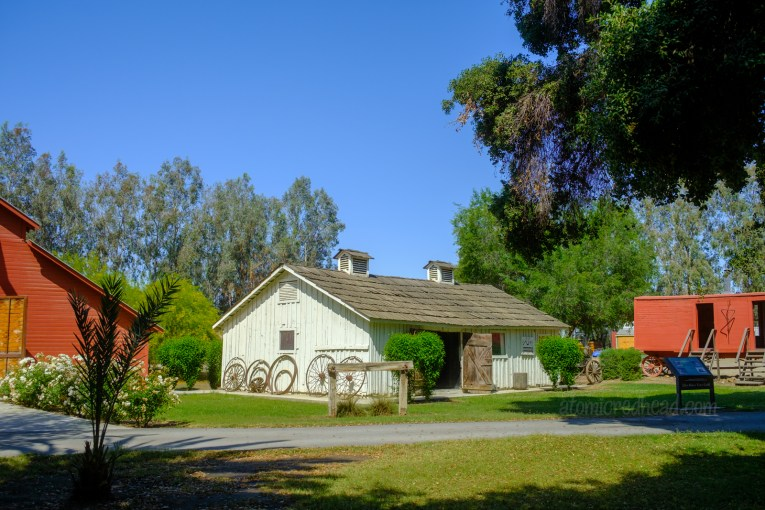 Exterior of the blacksmiths shop, a long white building. An array of wagon wheels sit along the side.
