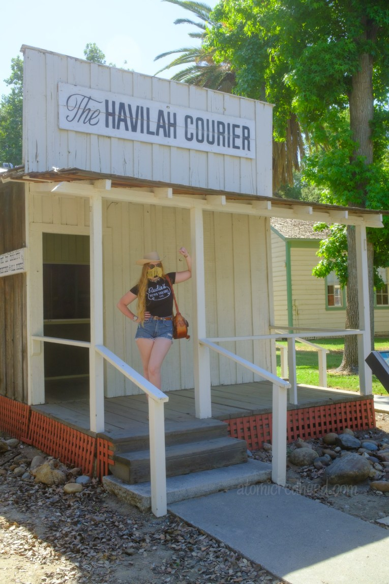 """Myself standing on the porch of the newspaper building, an old west style building painted white with black letters at the top reading """"The Havilah Courior"""", wearing a white cowboy hat, black shirt reading """"Nudie's Rodeo Tailor"""", jean shorts, and a tooled leather purse that resembles a saddle."""