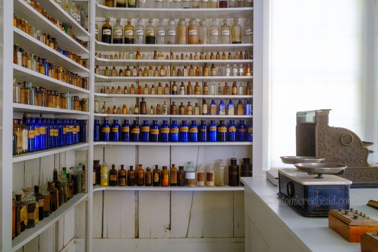 Inside the drug store, where a wide selection of glass bottles sit on shelves. Some are clear, others blue, and some brown.
