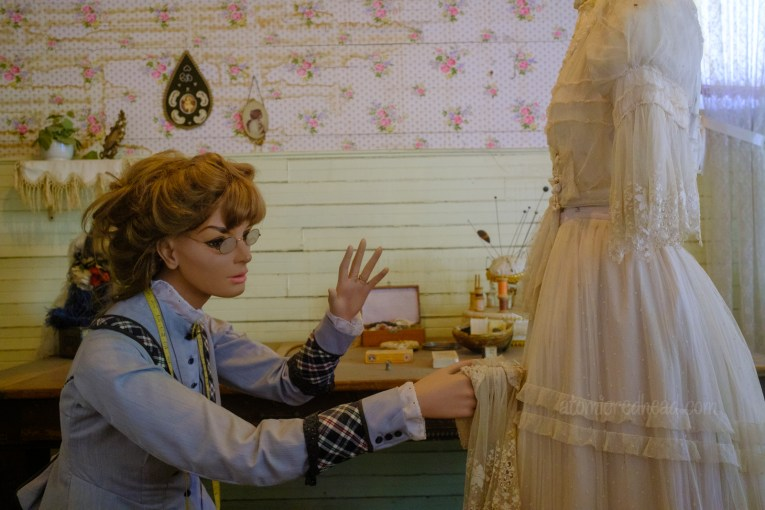 A mannequin of a woman appears as if she is working on a white dress that sits on a dressform.