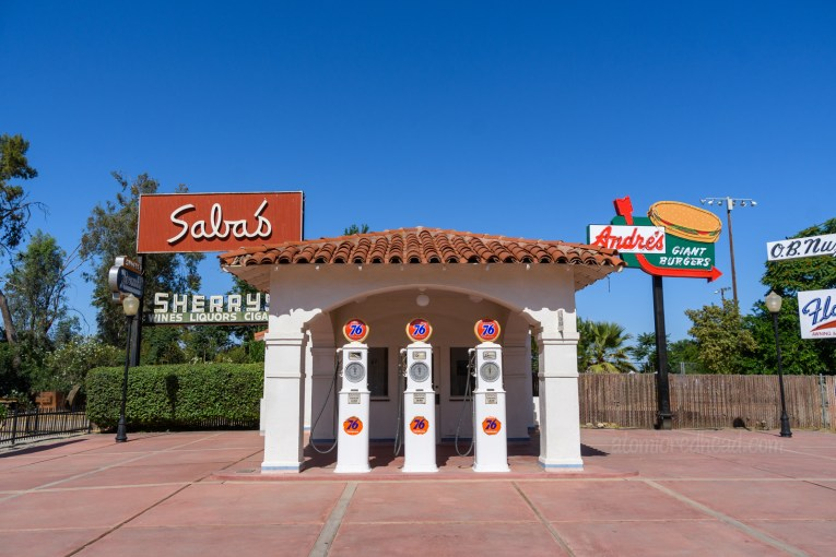 An old gas station from the 1930s, done in a Spanish Revival style with red tile roof and white stucco.