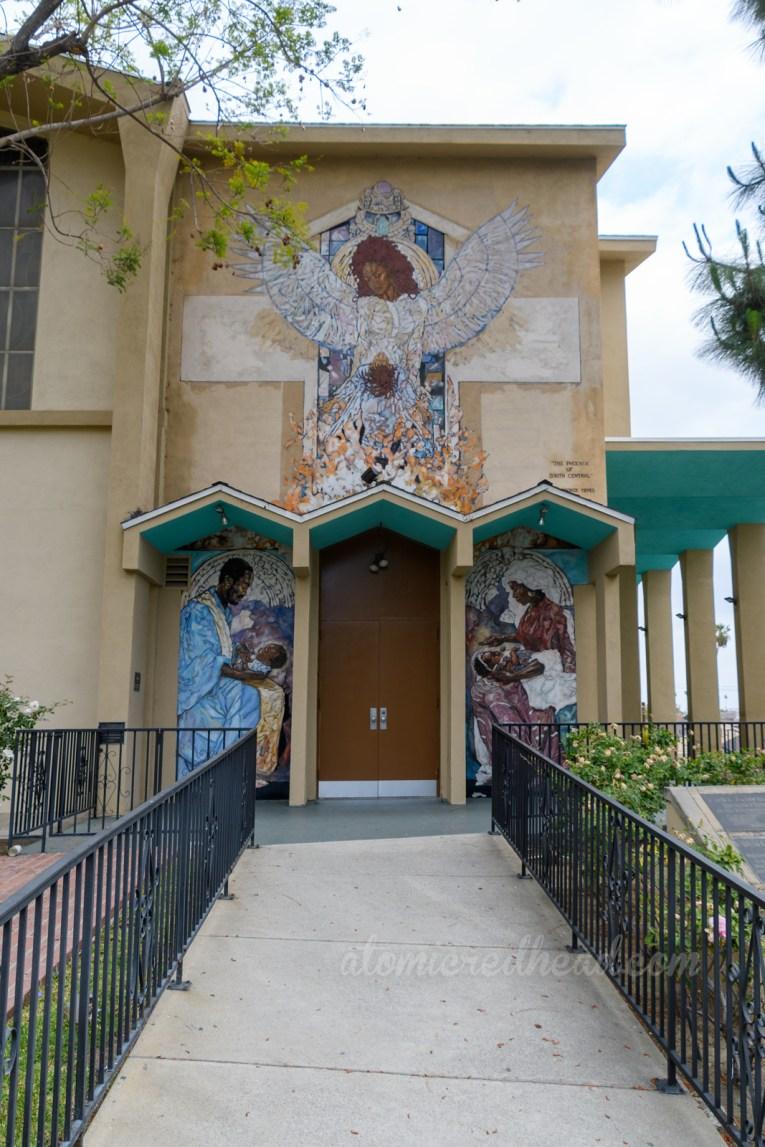 A mural of an angel over a zig-zag overhang for a door.