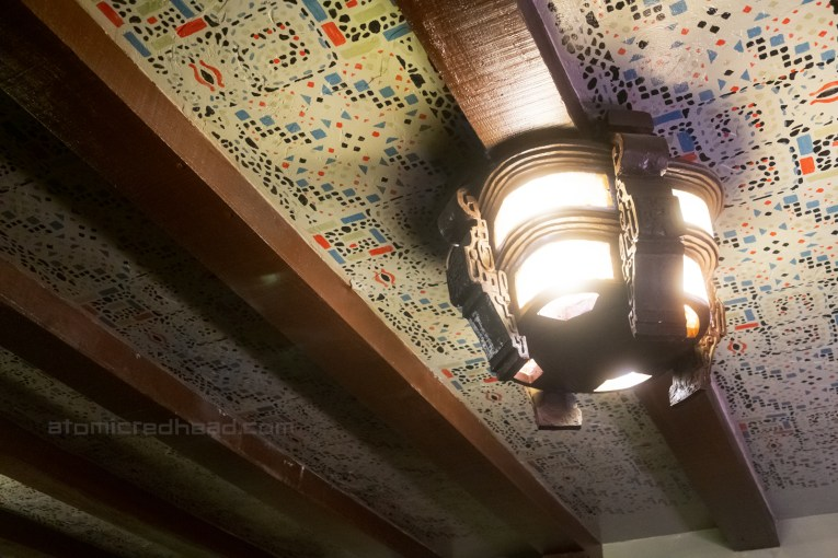 A carved wooden light fixture hangs from a heavily pattern ceiling.