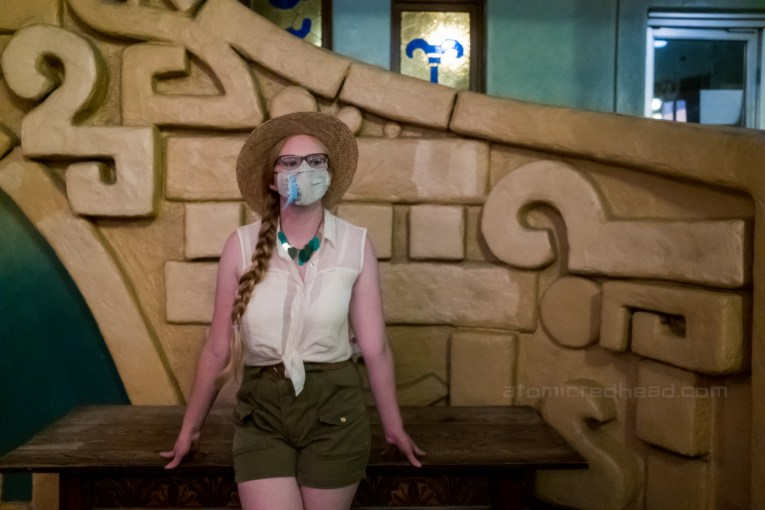 Myself, wearing a straw hat, white sleeveless blouse and green shorts, standing in front of the staircase.
