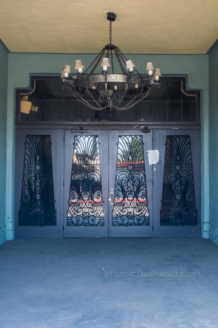 Entrance to the Aztec as seen from the outside. A wrought iron chandelier hangs from the ceiling. Doors with wrought iron swirls and patterns create a design atop the glass.