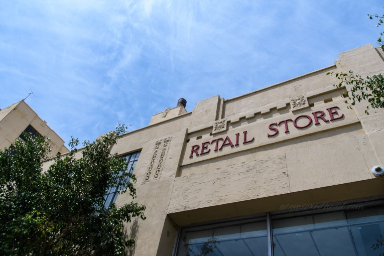 """Close-up of the store sign above the door reading """"Retail Store"""" in red letters."""