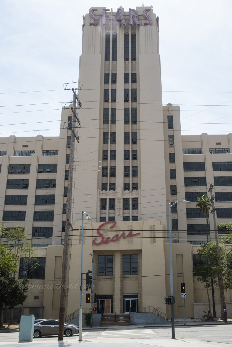 """Overall view of the front tower. Red script reading """"Sears"""" is just above the front doors. """"Sears"""" in art deco letters is at the very top of the tower."""