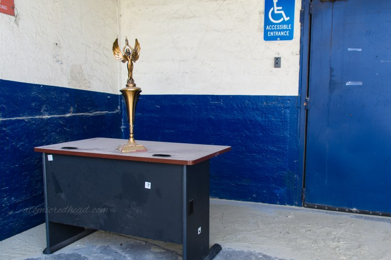 A dust covered desk with a trophy atop it.