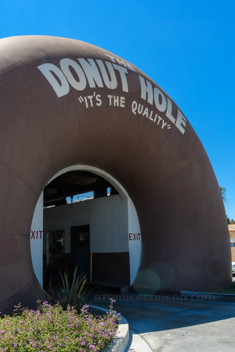 """Angled view of The Donut Hole, a massive brown donut rises from the ground, with an opening for cars to drive through. White text across the top reads """"The Donut Hole 'It's the Quality!'"""""""