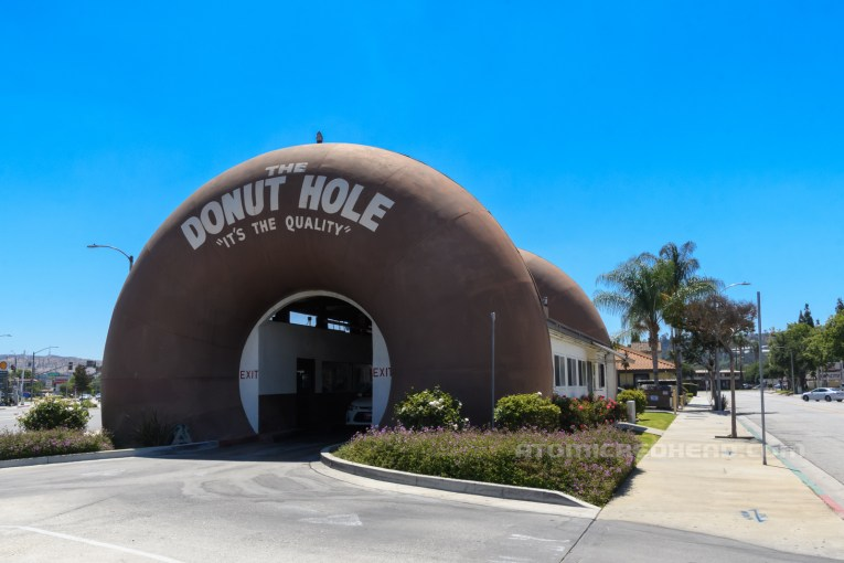 """Angled view of The Donut Hole, a massive brown donut rises from the ground, with an opening for cars to drive through. White text across the top reads """"The Donut Hole 'It's the Quality!'"""" To the right you can see the middle portion which is painted white and connects with the other donut."""