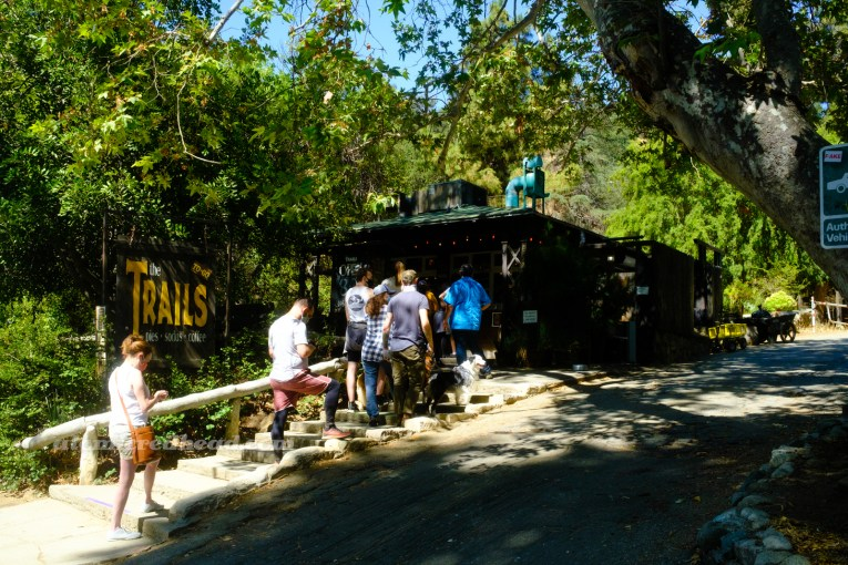 Exterior of The Trails, a small wooden building with a line of people waiting to order.