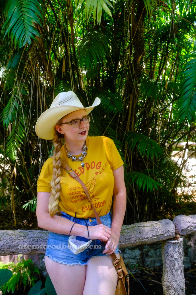 """Myself, wearing a cream straw cowboy hat, yellow shirt red text reading """"Red Dog California Cold Beer Restaurant Cocktails Good Vibes"""" and featuring a woman diving into a martini glass, and jean shorts, leaning against a railing made of concrete but made up to appear to be a log."""
