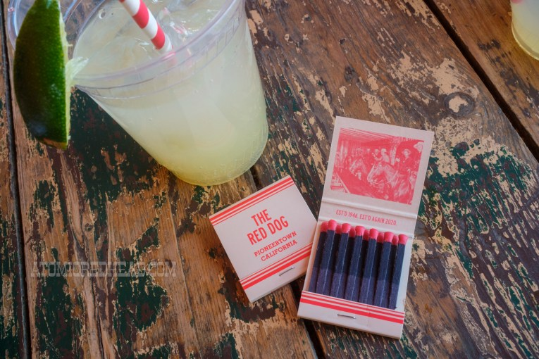 """House made lemonade in a cup, and a pair of matchbooks. The closed matchbook reads """"The Red Dog Pioneertown, California"""" the other is open and features an image of cowboys seated on horses at the bar. Text reads """"Est'd 1946 Est'd Again 2020"""""""