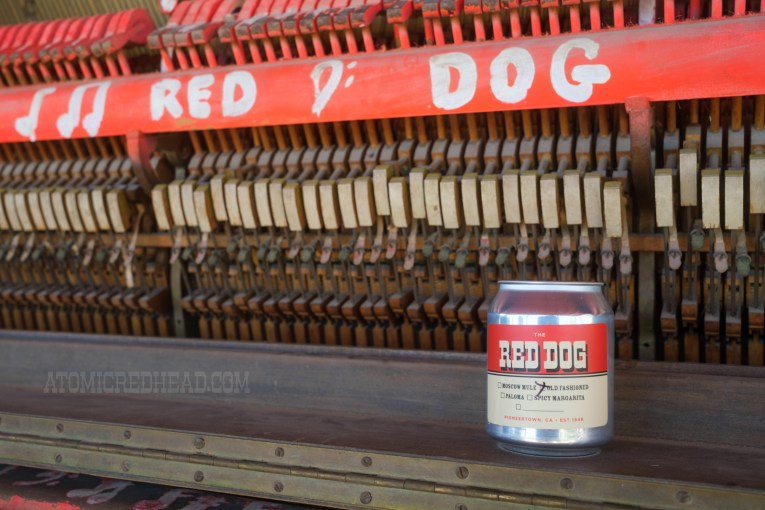 """An old piano sits on the porch, painted on it reads """"Red Dog"""" A small can reads """"Red Dog"""" and a small check list below indicates which to-go cocktail is inside."""