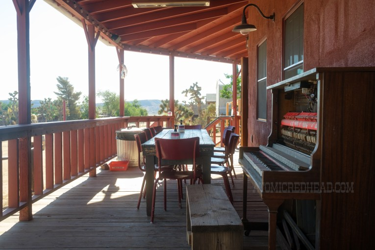 Covered outdoor patio seating, including a weather beaten piano.