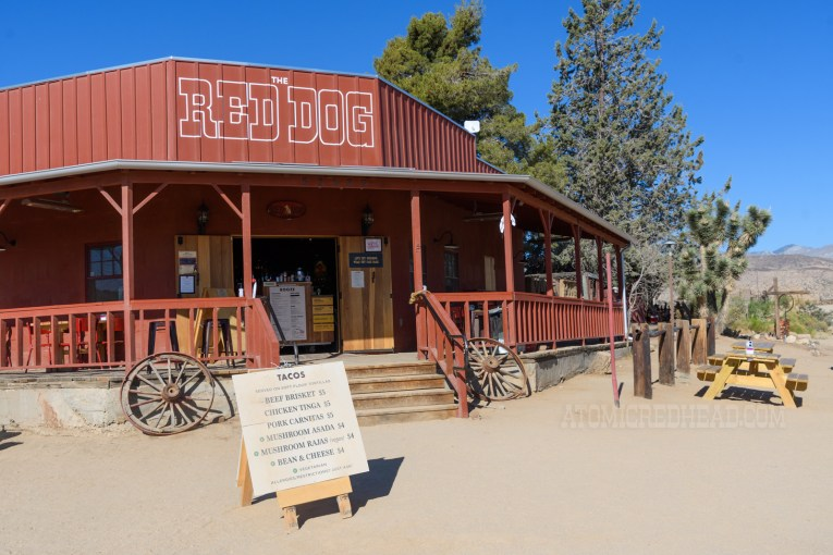 Front of the Red Dog, a dark red saloon with a full wrap around porch, with outdoor seating. Old wagon wheels flank the stairs up to the front door. A sandwich board out front displays their menu.
