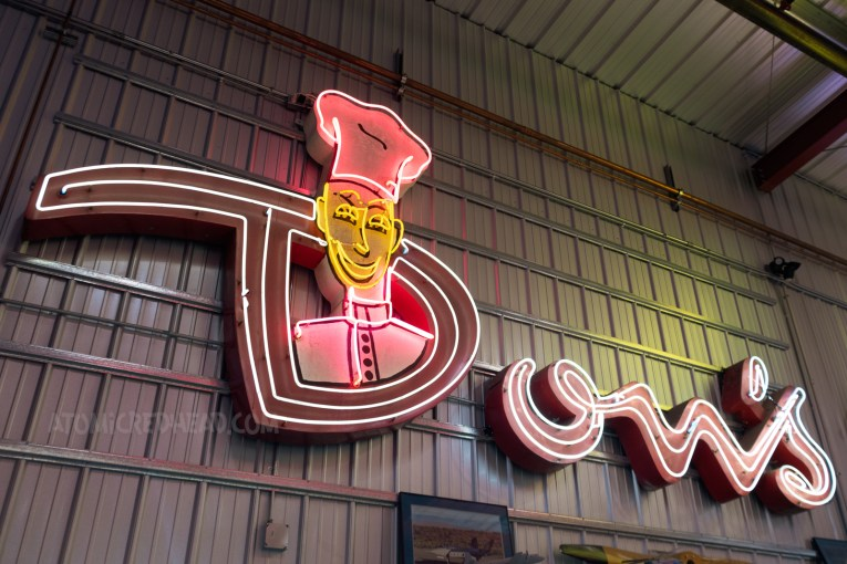 """A large neon sign that reads """"Don's"""" in a script. A neon chef pops up from the middle of the letter D."""