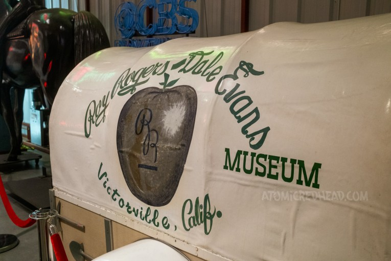 """A car trailer shaped like a covered wagon. Green script reads """"Roy Rogers & Dale Evans Museum Victorville, California."""""""