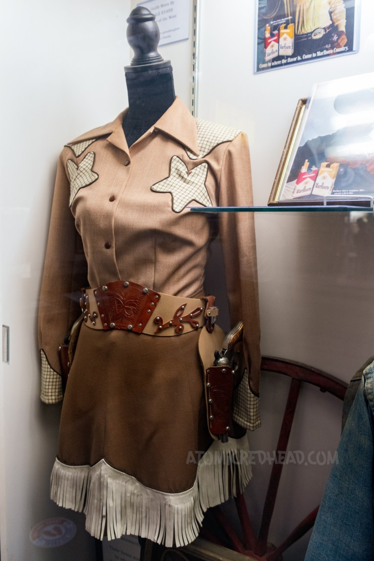 A lovely light brown western wear set of shirt and skirt. The shirt features two white stars near the shoulders and the skirt features white fringe, the set belonged to Dale Evans.