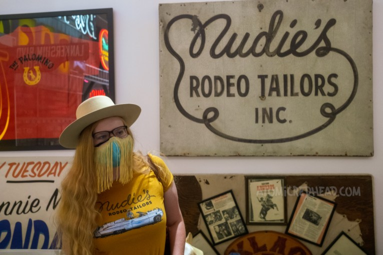 """Myself, wearing a cream cowboy hat, yellow shirt with a large white Cadillac and script reading """"Nudie's Rodeo Tailor"""" standing in front of a sign reading """"Nudie's Rodeo Tailor Inc."""""""