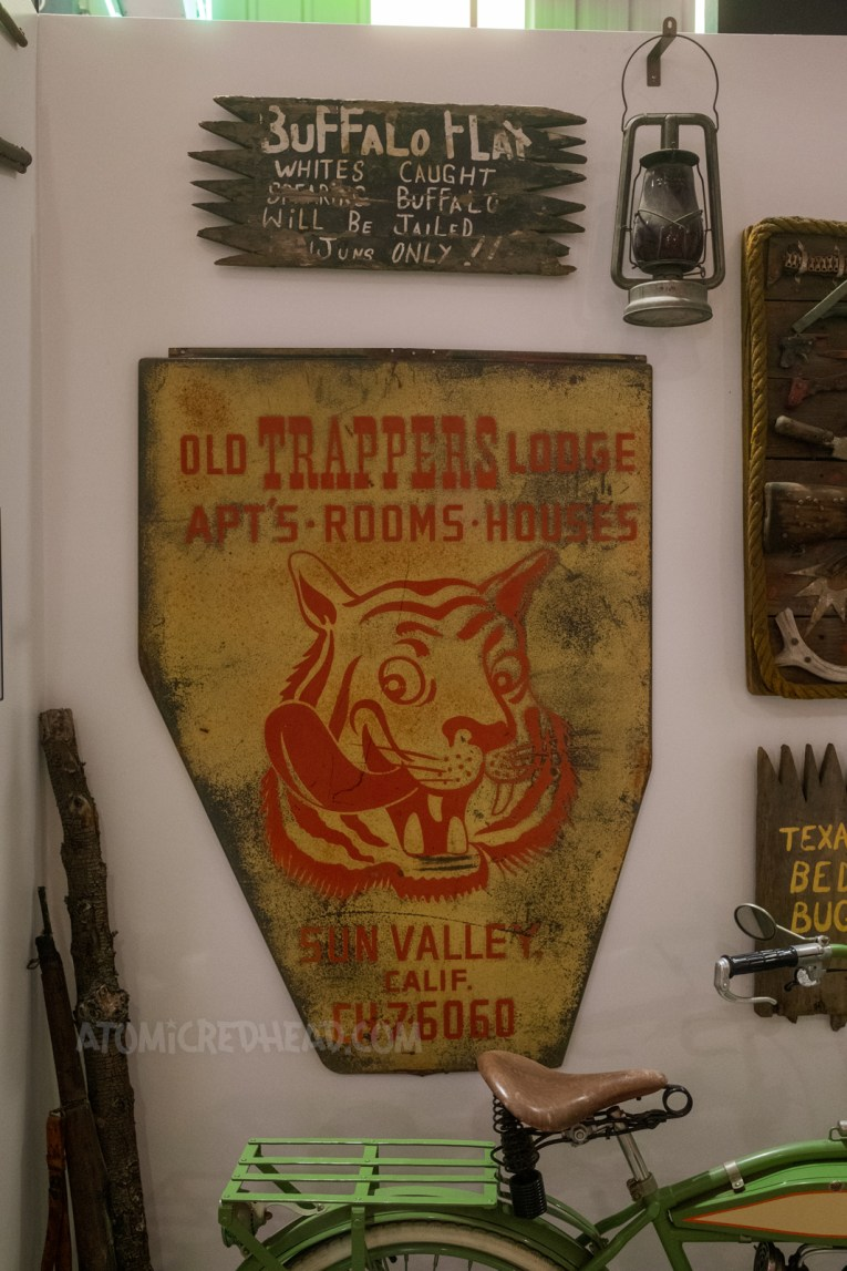 """Two signs hang on a wall. One is on an old, broken piece of wood and reads """"Buffalo Flat Whites caught spearing buffalo will be jailed! Injuns only!"""" The other is yellow and features an image of a tiger. In red letters it reads """"Old Trapper's Lodge Apt's Rooms Houses Sun Valley, Calif."""""""
