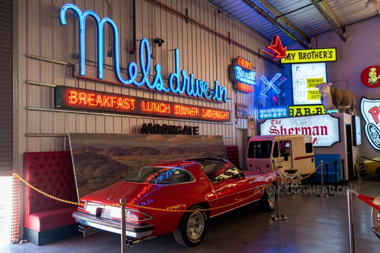 """A red Chevy Camaro sits under a blue neon sign reading """"Mel's drive in"""" with smaller red neon """"Breakfast Lunch Dinner Late Night"""""""