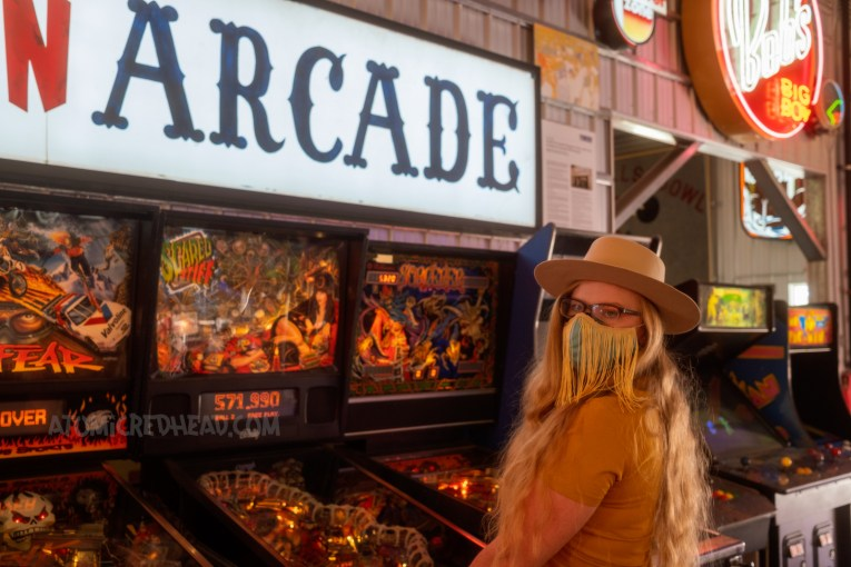 """Myself by an Elvira pinball machine. A back lit plastic sign reading """"ARCADE"""" in large blue letters above."""