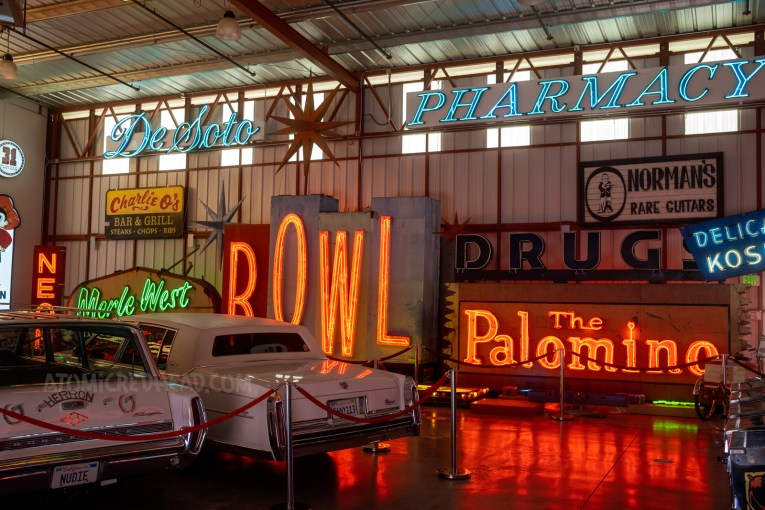 """Rear ends of cars jut out from the left side of the frame. Blue neon reading """"DeSoto Pharmacy"""" hangs near the ceiling. Large red neon spelling """"BOWL"""" and the neon sign for the Palomino."""