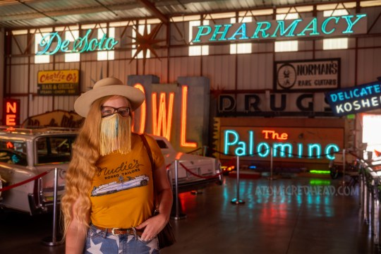 """Myself, wearing a cream cowboy hat, yellow shirt with a large white Cadillac and script reading """"Nudie's Rodeo Tailor"""" and jean shorts with white stars, standing in front of blue neon reading """"DeSoto Pharmacy"""" hangs near the ceiling. Large red neon spelling """"BOWL"""" and the neon sign for the Palomino."""