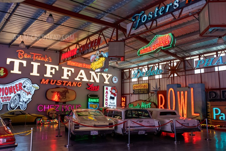 Overall view of one of the rooms at Valley Relics, including cars, and a variety of neon signs.