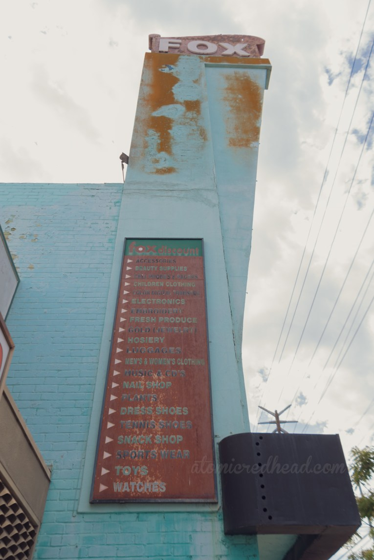 """On the side of the Fox Discount Department Store is a red faded sign listing the variety of items available within, """"Accessories, Beauty Supplies, Cell Products & Pagers, Children's Clothing, Color Digital Transfer, Electronics, Embroidery, Fresh Produce, Hosiery, Luggages, Men's & Women's Clothing, Music & CDs, Nail Shop, Plants, Dress Shoes, Tennis Shoes, Snack Shop, Sports Wear, Toys, Watches"""""""