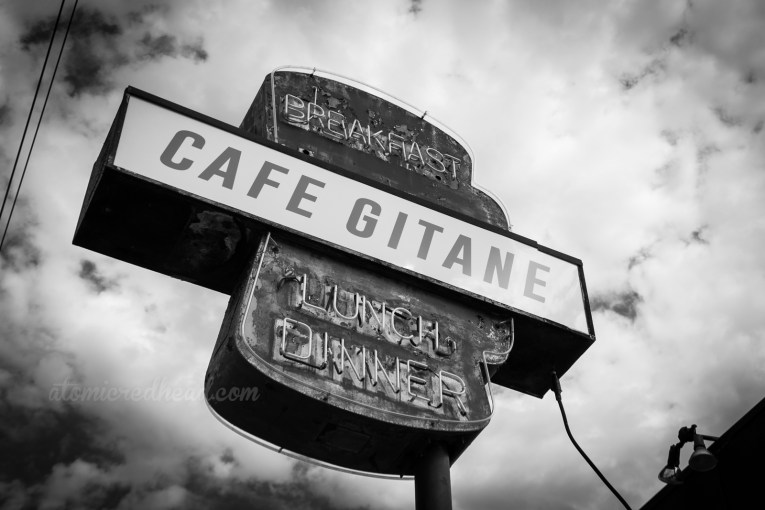 """Black and white photo of an hourglass like shape with a white backlit plastic section across the middle which reads """"Cafe Gitane"""" above the plastic reads """"breakfast"""" and below it """"Lunch Dinner"""" all in neon."""