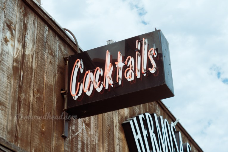 """A small black sign reads """"Cocktails"""" in red neon."""