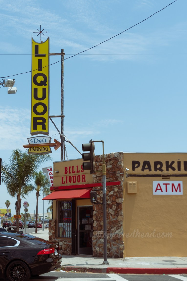 """A mustard yellow building features a corner door with golden brown rocks down the side. Coming up from the building is a backlit plastic sign reading """"Liquor Deli Parking"""" and features a neon arrow."""