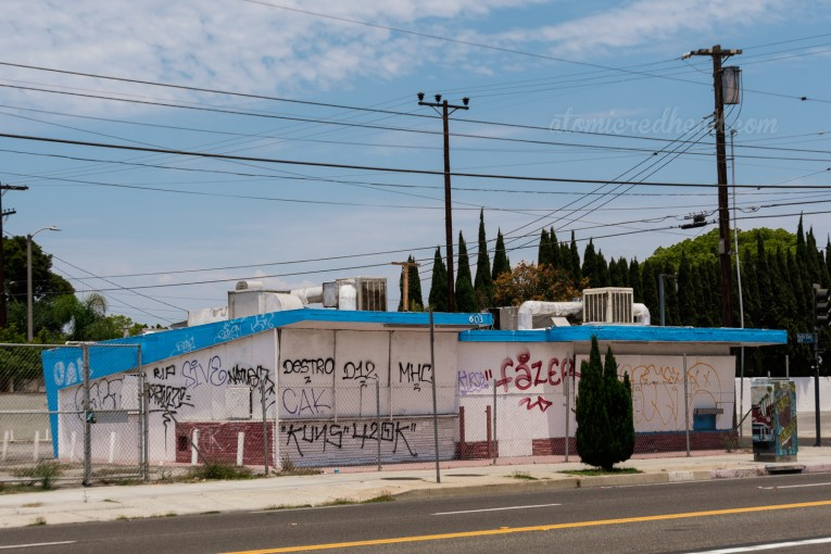 Behind a chainlink fence sits a boarded up building, painted white with blue trim, and covered in graffiti.