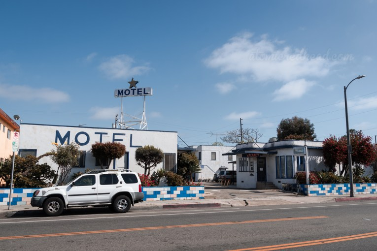 """The Golden Star Motel, a cluster of white buildings with blue trim. """"MOTEL"""" is painted on the side of one. The office is a curved deco style building and features a small """"No Vacancy"""" neon."""