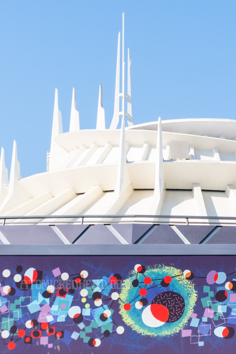 The white spires of Space Mountain rise above an abstract painting.