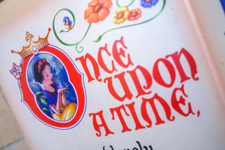 """Close-up of a book in front of the Snow White ride, which reads """"Once Upon a Time"""" in red script. Inside the """"O"""" is Snow White holding an apple."""