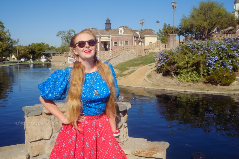 """Myself, wearing a blue peasant top with a bandana print on it, a red skirt with """"76"""" in white scattered throughout, and white shoes, standing in front of an old New England style building."""